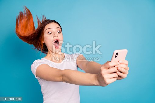 istock Portrait of her she nice attractive lovely cheerful cheery girlish crazy funny lady wearing white t-shirt making taking selfie post isolated on bright vivid shine blue background 1147991499