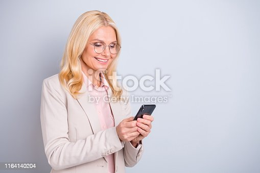 istock Portrait of her she nice attractive lovely stylish cheerful cheery glad wavy-haired lady holding in hands device web site surfing free time isolated over light white gray pastel background 1164140204