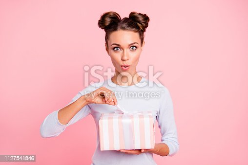 istock Portrait of her she nice attractive lovely sweet winsome glamorous cheerful glad girl holding in hands opening bow ribbon box isolated over pink pastel background 1127541846