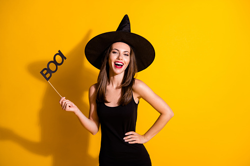 Portrait of her she nice attractive pretty charming cheerful cheery lady, wizard holding in hand glasses boo having fun festival isolated bright vivid shine vibrant yellow color background