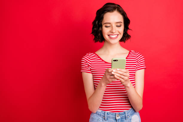 Portrait of her she nice attractive pretty lovely cheerful cheery addicted wavy-haired teen girl spending free time using wi-fi isolated over bright vivid shine red background stock photo
