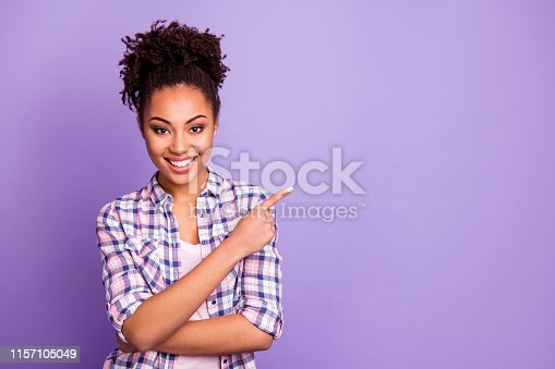Portrait of her she nice charming cute attractive lovely cheerful wavy-haired, girl in checked shirt showing aside ad advert product copy space isolated over violet purple pastel background