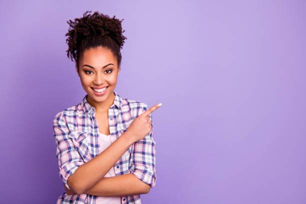 彼女の素敵な素敵な魅力的な魅力的な魅力的な素敵な陽気な波状の髪の女の子は、紫色の紫色のパステルの背景の上に隔離された広告製品のコピースペースを脇に示すチェックシャツで - 指差す ストックフォトと画像