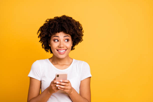 portrait of her she nice cute attractive lovely charming cheerful cheery wavy-haired lady holding in hands cell looking aside isolated on bright vivid shine yellow background - mandare un sms foto e immagini stock