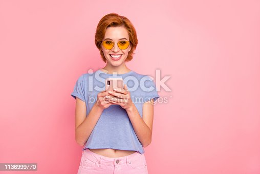 istock Portrait of her she nice cute charming attractive lovely sweet winsome cheerful cheery girl wearing casual blue t-shirt yellow glasses holding in hands cell isolated on pink pastel background 1136999770