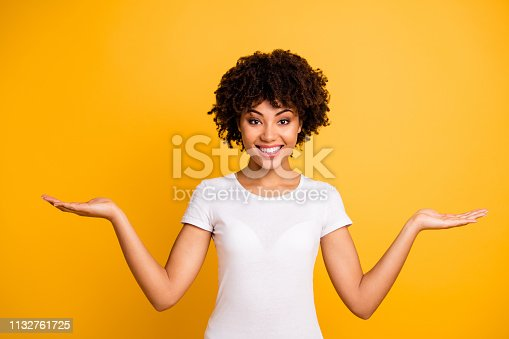 istock Portrait of her she nice cute lovely attractive cheerful cheery optimistic wavy-haired girl holding two palms copy space isolated on bright vivid shine yellow background 1132761725