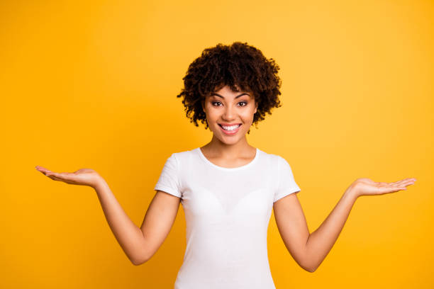 portrait of her she nice cute lovely attractive cheerful cheery optimistic wavy-haired girl holding two palms copy space isolated on bright vivid shine yellow background - balance foto e immagini stock