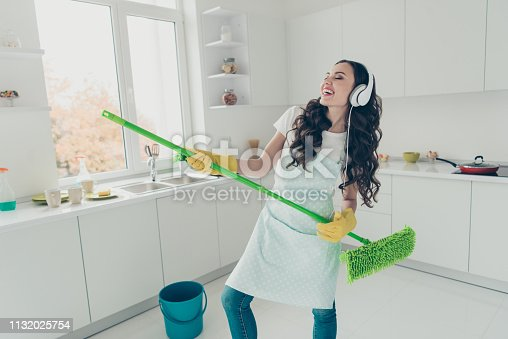 1081403344 istock photo Portrait of her she nice cute lovely beautiful cheerful positive wavy-haired house-wife using broom dancing having fun fooling in modern light white interior indoors 1132025754