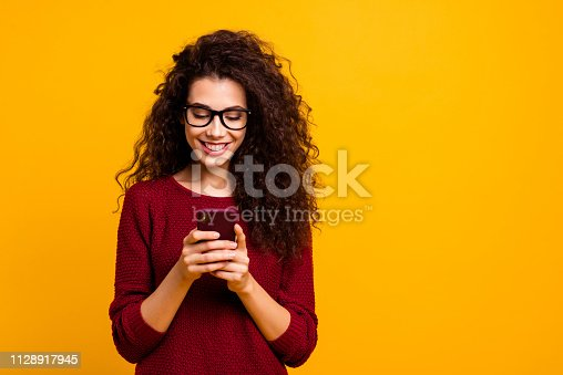 Portrait of her she nice lovely attractive pretty cheerful cheery wavy-haired lady holding in hands cell playing game free time isolated over bright vivid shine orange background