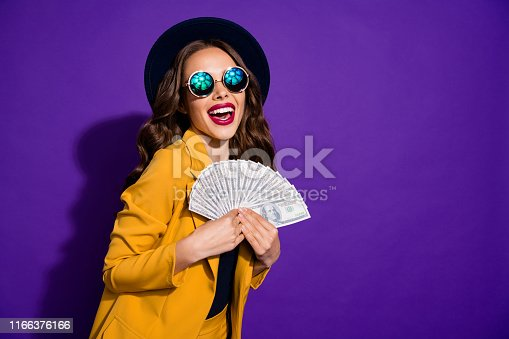 Portrait of her she nice lovely cheerful cheery glad rich wealthy wavy-haired, lady holding in hands large budget sum grant lottery win isolated over bright vivid shine violet lilac background