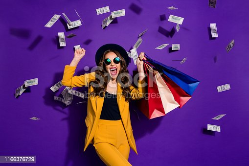 istock Portrait of her she nice lovely cheerful cheery glad wavy-haired lady shopaholic carrying bags flying 100 million budget salary success isolated over bright vivid shine violet lilac background 1166376729