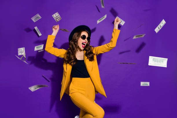 Portrait of her she nice lovely trendy cheerful rich wealthy wavy-haired lady winner currency flying 100 million budget winning isolated over bright vivid shine violet lilac background stock photo