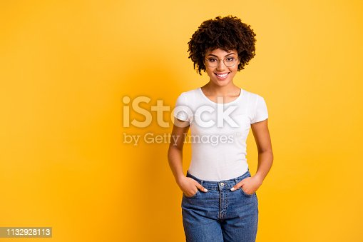 Portrait of her she nice smart clever attractive beautiful cheerful positive wavy-haired lady holding hands in pockets isolated over bright vivid shine yellow background.