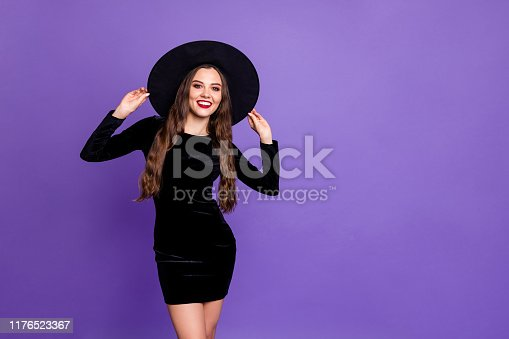 Portrait of her she nice-looking attractive fascinating glamorous cheerful long, haired lady touching hat isolated over bright vivid shine vibrant blue violet purple lilac color background