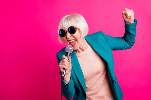 porträtt av henne hon snygg attraktiv härlig glad gråhåriga damen sjunger cool hit tillbringa helgen isolerad på ljusa levande glans pulserande rosa fuchsia färg bakgrund - celebrities of age bildbanksfoton och bilder