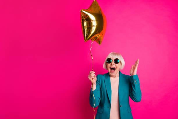 porträtt av henne hon snygg attraktiv härlig galen överlycklig glad glada gråhåriga lady håller ballong ha roligt isolerade på ljusa levande glans pulserande rosa fuchsia färg bakgrund - celebrities of age bildbanksfoton och bilder