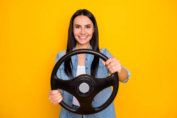 Portrait of her she nice-looking attractive lovely pretty charming cheerful brunet girl turning steering wheel isolated on bright vivid shine vibrant yellow color background stock photo