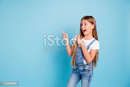 istock Portrait of her she nice-looking cute attractive cheerful amazed glad straight-haired blonde girl pointing two fingers aside copy space isolated on blue pastel background 1132006261