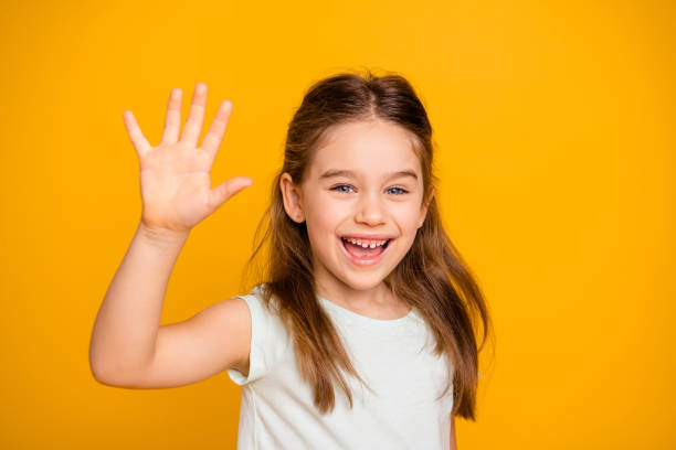 portrait of her she nice-looking cute attractive lovely pretty cheerful cheery positive pre-teen girl waving hi hello greetings i'm here isolated over bright vivid shine yellow background - sventolare la mano foto e immagini stock