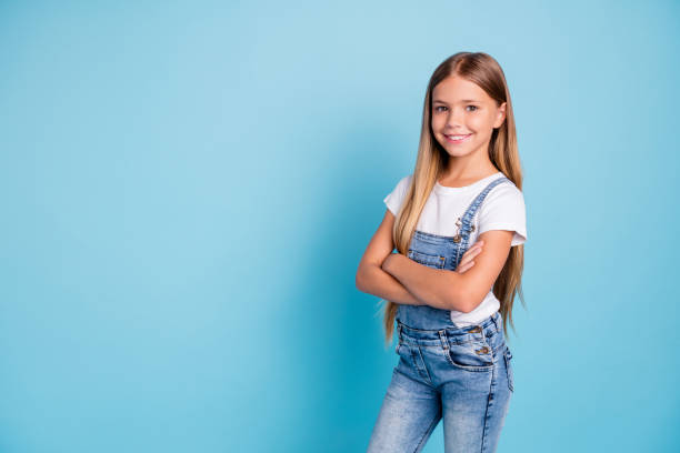 Portrait of her she nice-looking cute lovely attractive cheerful cheery straight-haired blonde girl folded arms copy space isolated on blue pastel background Portrait of her she nice-looking cute lovely attractive cheerful cheery straight-haired blonde girl folded arms copy space isolated on blue pastel background. bib overalls stock pictures, royalty-free photos & images