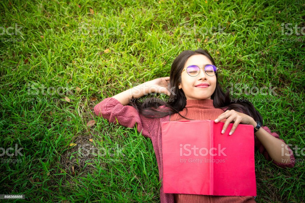 Portrait of high school girl lay down and read a book in park,...