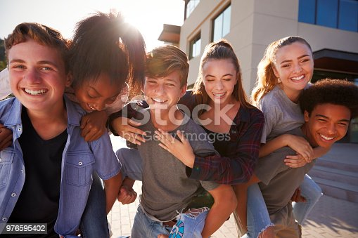 Portrait Of High School Students Giving Each Other Piggybacks College Buildings
