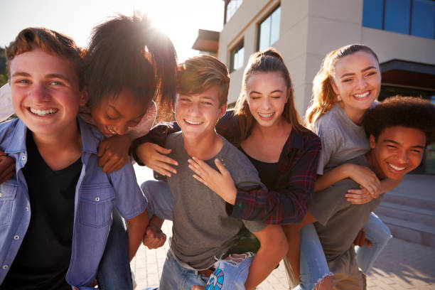 portrait of high school students giving each other piggybacks college buildings - ragazzi adolescenti foto e immagini stock