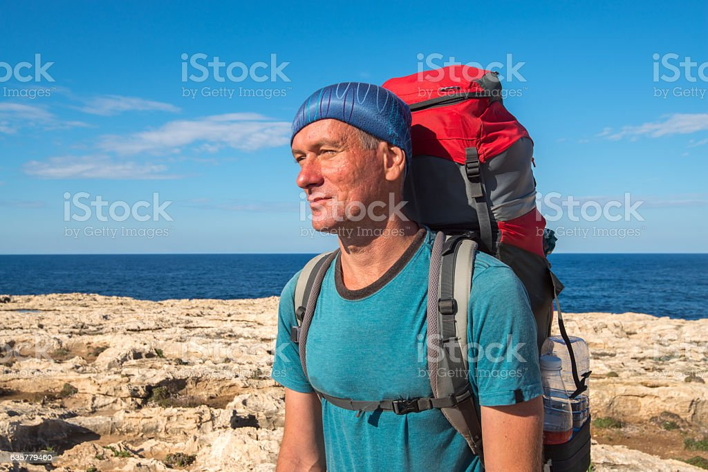 Portrait of hiker with backpack on rocky coast stock photo