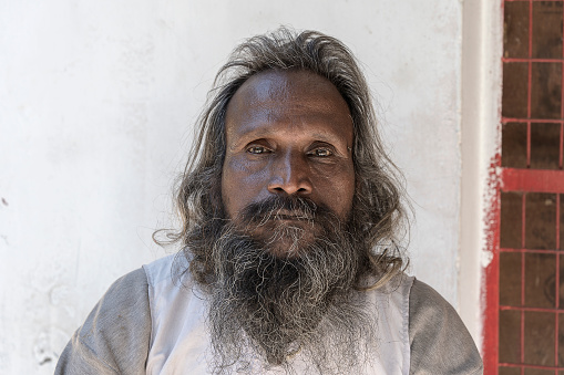 Portrait of Hindu sadhu holy man, sits on the ghat and asks for alms from passers-by near the Ganges river in Rishikesh, India, close up