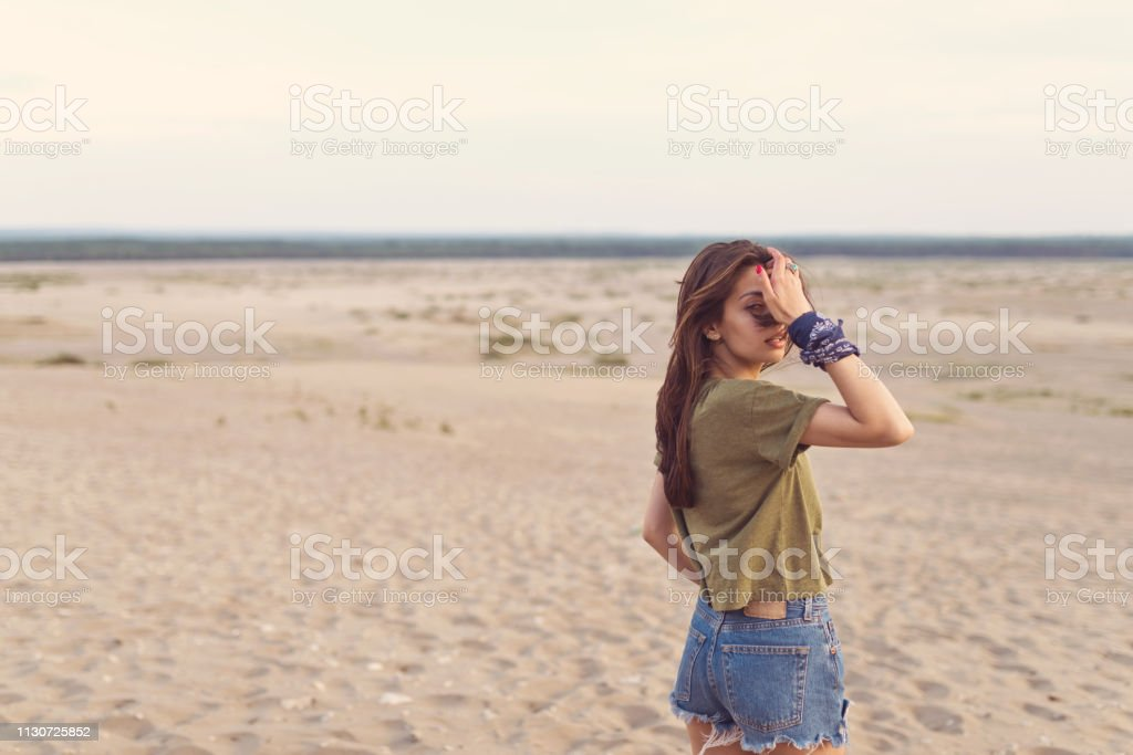 Portrait of hipster adjusting hair in desert Portrait of hipster adjusting hair in desert. Young female is enjoying summer vacation on arid landscape. beautiful woman is standing on sand. 25-29 Years Stock Photo