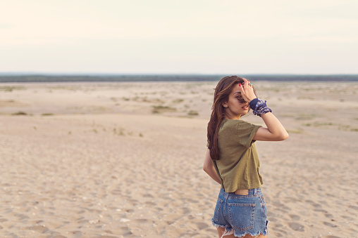Portrait Of Hipster Adjusting Hair In Desert Stock Photo - Download Image Now