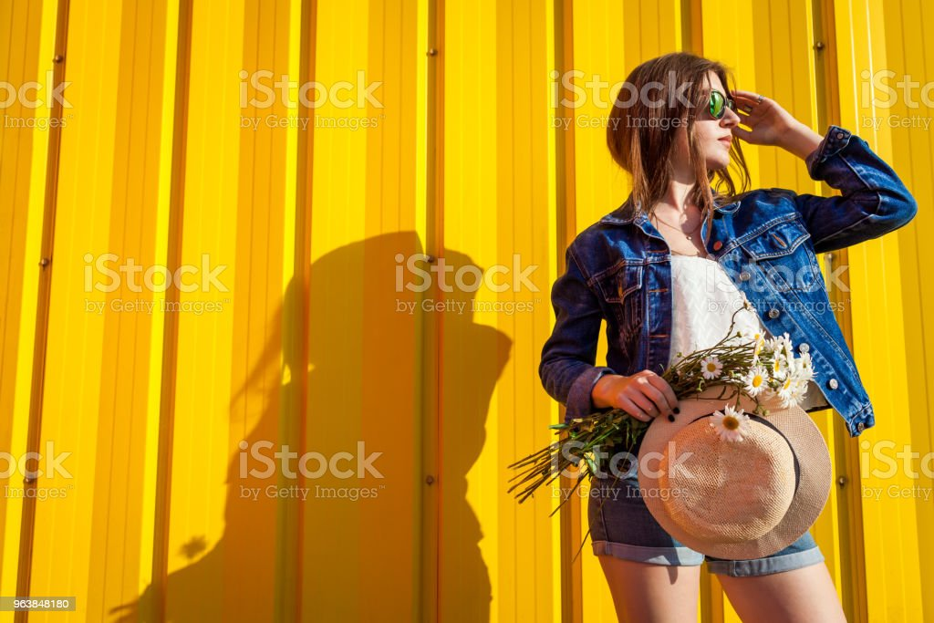 Portrait of hipster girl wearing glasses and hat with flowers against yellow background. Summer outfit. Fashion. Space. - Royalty-free Adult Stock Photo