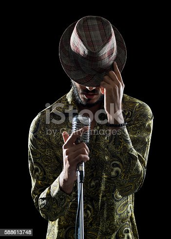 Portrait of hipster man wearing an old fashioned shirt and hat singing in dark via microphone.He is holding microphone with right hand and touching his hat with left hand.Isolated on black with clipping path.Shot in studio with medium format DSLR camera Hasselblad.