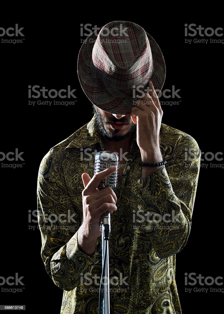 Portrait Of Hipster Man Singing While Touching His Hat stock photo