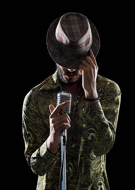 portrait of hipster man singing while touching his hat - ポップミュージシャン ストックフォトと画像