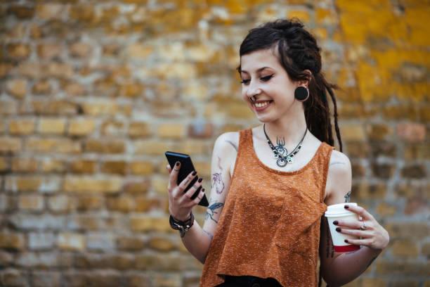 porträt von hipster junge frau mit smartphone für kommunikation - ohrringe piercing stock-fotos und bilder