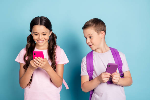 Portrait of his he her she attractive small little focused curious cheerful friends friendship using gadget 5g app blogging chatting guy peeking isolated blue pastel color background stock photo