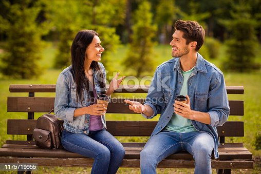Young cute heterosexual couple holding social distance on park bench and wearing protective face masks. Small dog sitting between them.