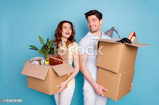 istock Portrait of his he her she nice-looking attractive cheerful cheery glad people carrying big large boxes packages buyings isolated over bright vivid shine blue green background 1164876185