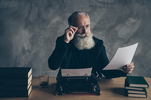 Portrait of his he nice attractive bearded focused concentrated gray-haired, professional expert creative publisher reading news life story article essay over concrete wall background