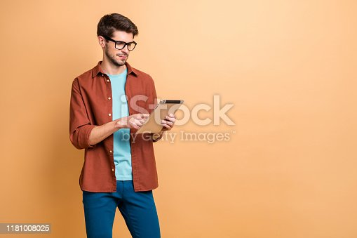 istock Portrait of his he nice attractive calm focused successful content brunet guy holding in hands reading digital e-book isolated over beige color pastel background 1181008025