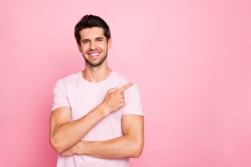 istock Portrait of his he nice attractive cheerful cheery confident content glad guy pointing forefinger aside promotion surprise gift present advert ad isolated over pink pastel background 1164339810