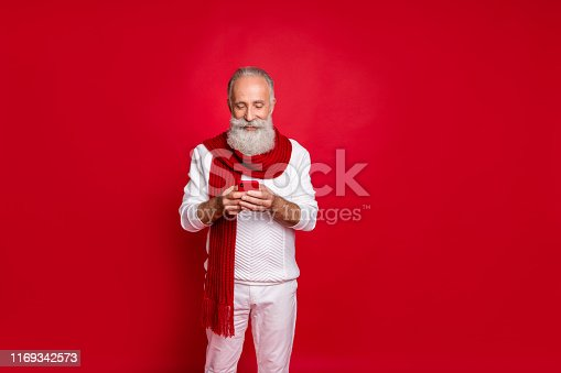 istock Portrait of his he nice attractive cheerful cheery focused gray-haired man holding in hands cell chatting internet online isolated over bright vivid shine red background 1169342573