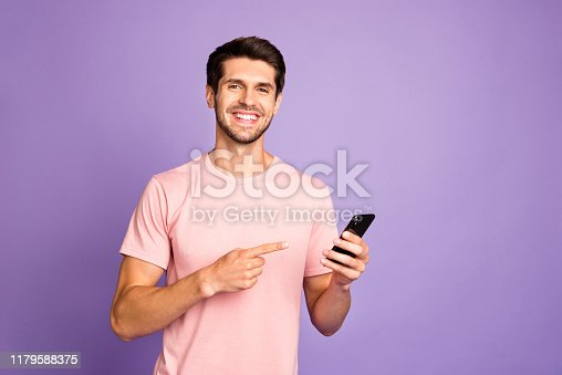 istock Portrait of his he nice attractive cheerful cheery glad content guy wearing pink tshirt holding in hands recommending digital device isolated on violet purple lilac pastel color background 1179588375