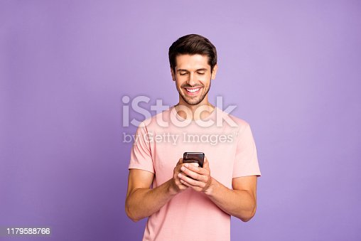 istock Portrait of his he nice attractive cheerful cheery guy wearing pink tshirt holding in hands using 5g app cell modern technology isolated over violet purple lilac pastel color background 1179588766