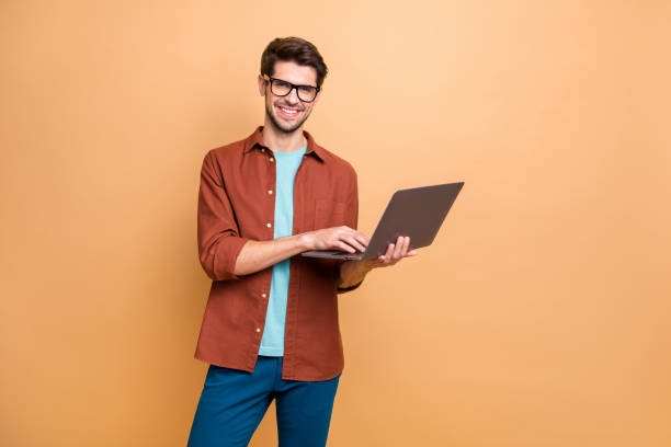 Portrait of his he nice attractive cheerful cheery successful content smart clever brunet guy agent broker holding in hands laptop working isolated over beige color pastel background stock photo
