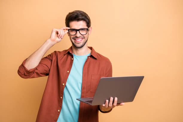 Portrait of his he nice attractive cheerful cheery successful content brunette guy holding in hands laptop working part-time touching specs isolated over beige color pastel background stock photo