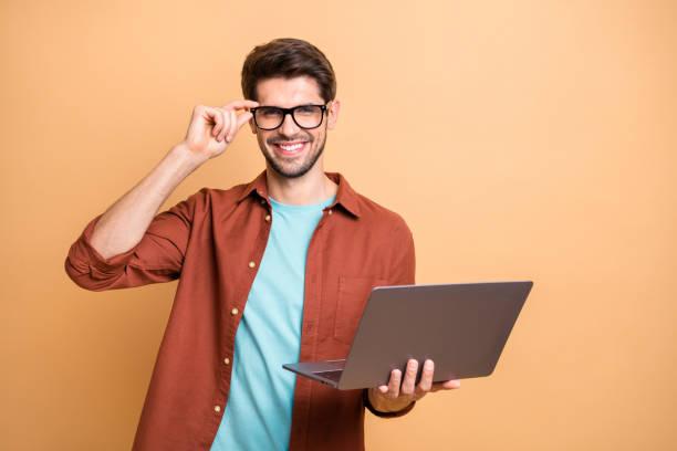 Porträt seiner er schöne attraktive fröhliche fröhliche erfolg Brünette Kerl hält in den Händen Laptop arbeiten Teilzeit berühren Spezifiken isoliert über Beige Farbe Pastell Hintergrund – Foto