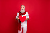 istock Portrait of his he nice attractive confident cheerful cheery gray-haired man holding in hands healthy heart health care medicine medicare isolated over bright vivid shine red background 1169343128