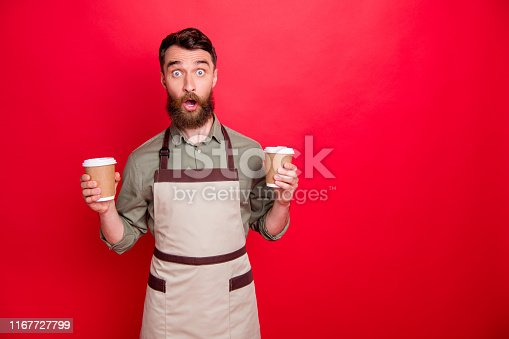 istock Portrait of his he nice attractive confused stunned wondered bearded guy waiter holding in hands cappuccino espresso latte choose choice isolated over bright vivid shine red background 1167727799